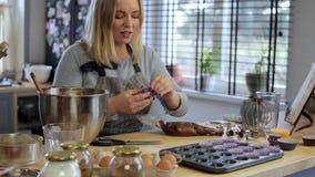 Белокурая женщина кладя бумажные стаканчики оболочек в блюдо выпечки Женщина варя пирожные Промежуток времени сток-видео