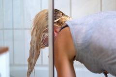 Белокурая женщина моя ее волосы в bathroom стоковое изображение