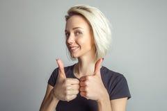 Белокурая женщина показывает 2 большого пальца руки вверх Стоковая Фотография