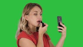 Белокурая женщина прикладывая губную помаду смотря в телефоне на зеленом экране, ключ chroma видеоматериал