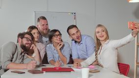 Белокурая женщина принимает selfie с ее коллегами в офисе, используя смартфоны сток-видео