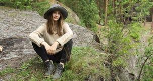 Белокурая женщина сидит ослаблять в лесе видеоматериал