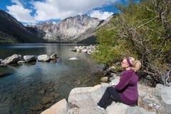 Белокурая женщина сидит самостоятельно озером каторжник в весеннем времени, расположенном US-395, около мамонтовых озер Калифорни стоковая фотография rf