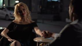 Белокурая женщина сидя в кафе с парнем, человек держа руку подруги сток-видео
