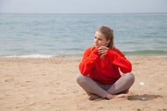 Белокурая женщина сидя на береге моря песчаного пляжа стоковое изображение