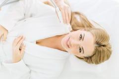 Белокурая женщина с длинными волосами делает лазер стороны resurfacing в центре красоты стоковая фотография
