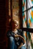 Белокурая красивая женщина представляя около витража Стоковое Фото