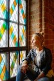 Белокурая красивая женщина представляя около витража Стоковое Изображение