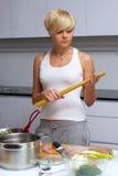 белокурая кухня девушки делая макаронные изделия милой Стоковое Изображение RF