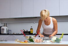 белокурая кухня девушки делая макаронные изделия милой стоковая фотография rf