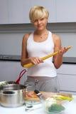 белокурая кухня девушки делая макаронные изделия милым стоковые изображения