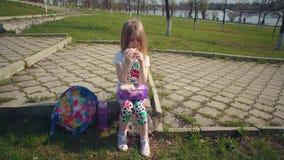 Белокурая маленькая девочка есть ее обед в парке на солнечный день видеоматериал