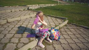 Белокурая маленькая девочка есть ее обед в парке на солнечный день акции видеоматериалы