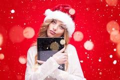 Белокурая модельная девушка в шляпе Санты над красным цветом Стоковые Изображения
