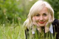 белокурая модель зеленого цвета травы счастливая сверх стоковое изображение