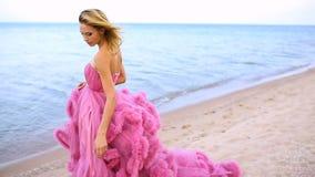 Белокурая молодая женщина для длиной изумляя платья белой розовой свадьбы сексуального на море видеоматериал