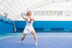 Белокурая молодая женщина играя теннис стоковые изображения