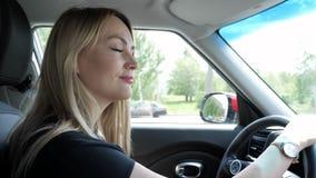 Белокурая молодая женщина управляет автомобилем в городе держа руки на руле акции видеоматериалы