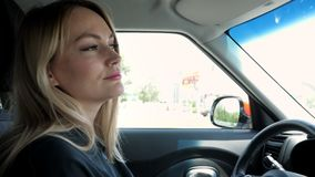 Белокурая молодая женщина управляет автомобилем в городе акции видеоматериалы