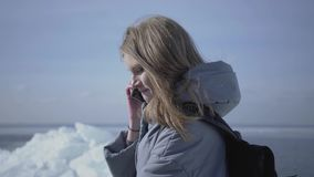 Белокурая привлекательная женщина вызывая к ее другу ее положением мобильного телефона на ледяном поле Турист перед акции видеоматериалы