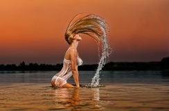 белокурая сексуальная женщина воды захода солнца Стоковая Фотография