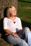 белокурая сидя грея на солнце женщина Стоковые Изображения RF