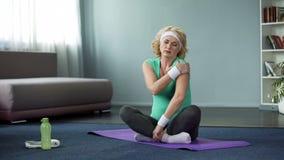 Белокурая старшая женщина в sportswear сидя на циновке йоги и массажируя ее плечо стоковое фото rf