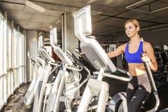 Белокурая sporty женщина в фитнес-клубе или спортзал, езда на orbitrack Стоковые Фото
