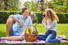Белокурое женское фото снимая ее парня на времени пикника Стоковое фото RF