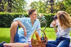 Белокурое женское фото снимая ее парня на времени пикника Стоковые Изображения RF