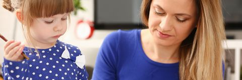 Белокурое усмехаясь владение маленькой девочки в щетке руки стоковые изображения