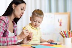 Белокурое усмехаясь владение мальчика в чертеже карандаша руки что-то вместе с мамой Стоковые Изображения RF