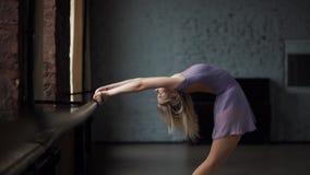 Белокурое ballerine тренирует ее отклонение около окна акции видеоматериалы