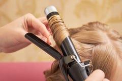 Белокурые волосы и завивая утюг стоковые фотографии rf