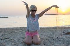 Белокурые игры женщины с песком Стоковые Изображения RF
