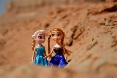 Белокурые куклы играют в песке и идут совместно в скалистую область Стоковое Изображение