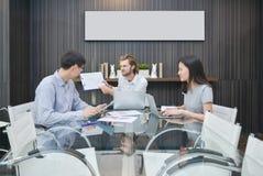 Белокурый бизнесмен обвиняя азиатского работника в конференц-зале стоковое изображение rf