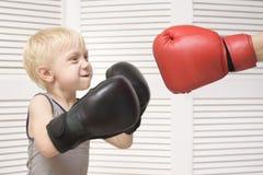 Белокурый бокс мальчика с рукой в красной перчатке взволнованности стоковое фото rf