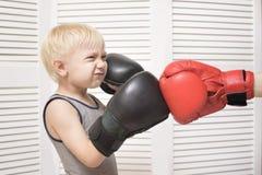 Белокурый бокс мальчика с рукой в красной перчатке взволнованности стоковые изображения