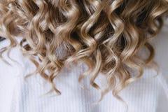 Белокурый взгляд девушки стиля причёсок от позади стоковое фото