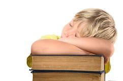 Белокурый мальчик на стоге книг стоковое фото rf