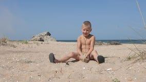 Белокурый мальчик сидя на песчаном пляже бросает вверх над его головой желтый песок видеоматериал