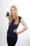 белокурый мобильный телефон девушки показывая усмехаться Стоковое фото RF