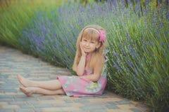 Белокурый молодой ребёнок имеет некоторую потеху во время праздников летних каникулов представляя встречу стиля моды близко к зел стоковое изображение rf