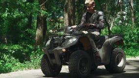 Белокурый подросток скачет на ATV и управляет прочь видеоматериал