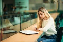 Белокурый телефон пользы девушки в библиотеке Стоковая Фотография