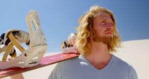 Белокурый человек при доска песка смотря расстояние в пустыне 4k акции видеоматериалы