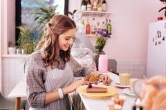 Белокур-с волосами сервер кофе подготавливая десерты для ее клиентов стоковая фотография rf