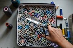 Белошвейка вытягивает пару ножниц из коробки с пасмами покрашенных потоков Шить индустрия стоковое изображение rf