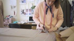 Белошвейка молодой женщины режет ткань с ножницами, в работая процессе, готовя таблицу с тканью на предпосылке акции видеоматериалы